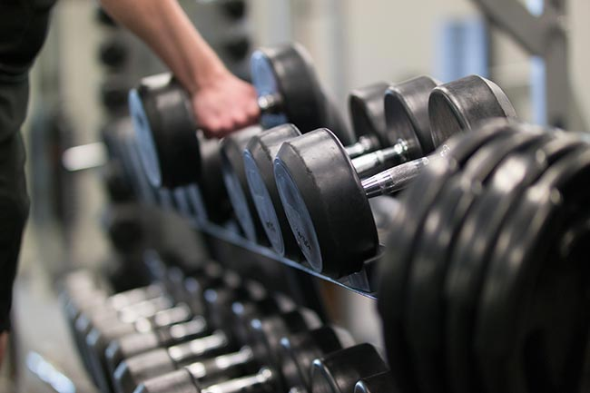 man using dumbbells at fitness club