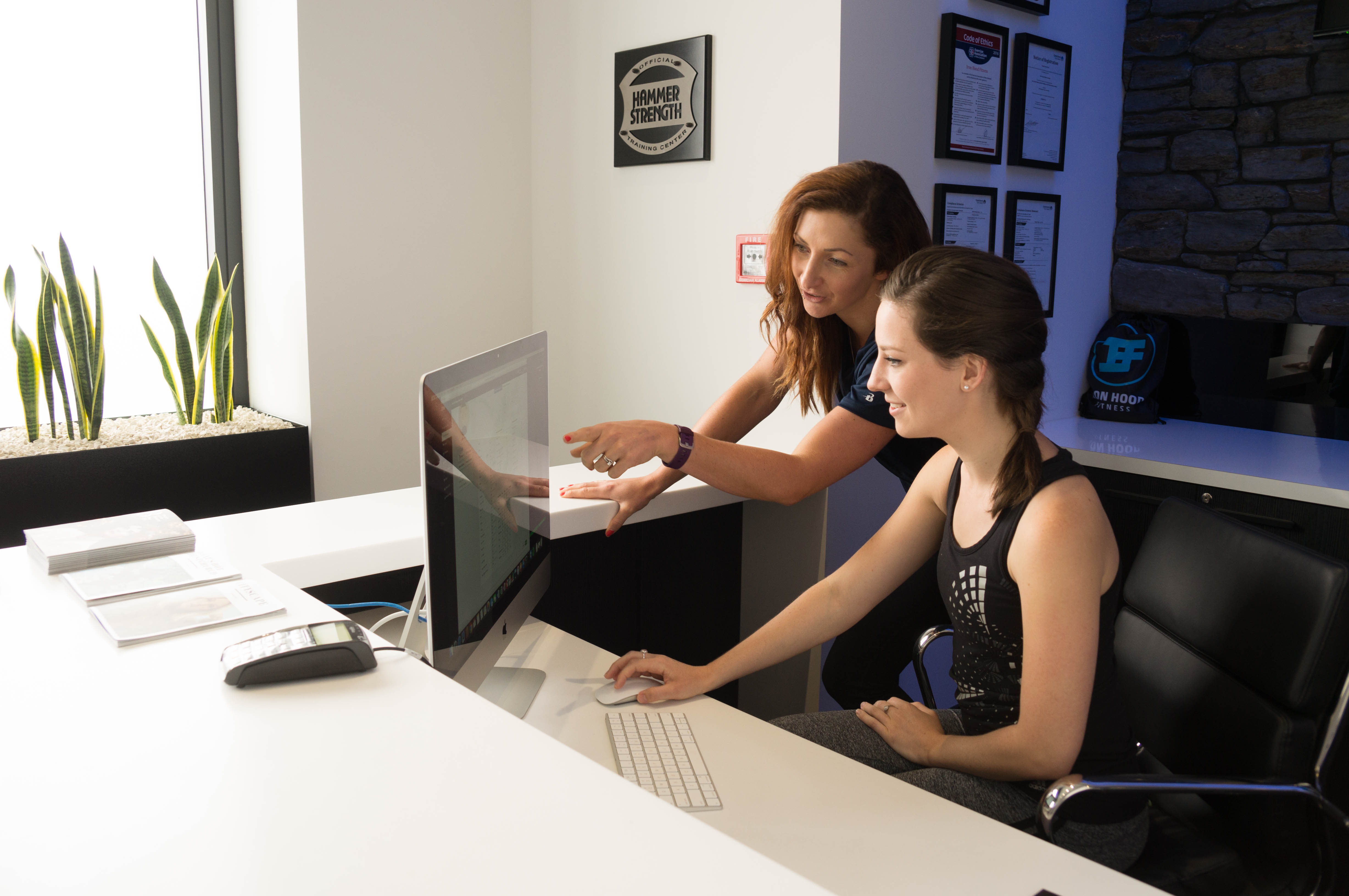 Woman being shown how to use fitness club management software to manager her fitness club