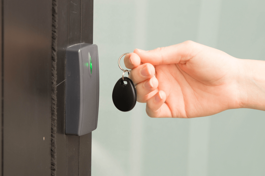 person swiping gym access control key tag